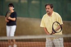 L'homme aîné joue au tennis Image stock