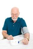 L'homme aîné prend sa tension artérielle Image stock