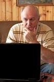 L'homme aîné travaille sur l'ordinateur portatif Photos libres de droits
