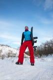 L'homme actif avec le surf des neiges détendant sur la neige a couvert la pente Images libres de droits