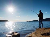 L'homme actif pêche sur la mer du contrôle rocheux de pêcheur de côte poussant l'amorce Images stock
