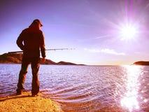 L'homme actif pêche sur la mer du contrôle rocheux de pêcheur de côte poussant l'amorce Photographie stock libre de droits