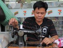 L'homme actionne Maching de couture dans le système de textiles Images libres de droits