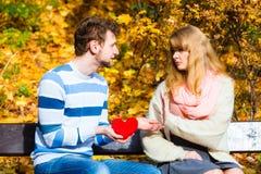 L'homme admettent l'amour à la fille sur le banc en parc Photos stock