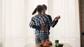 L'homme adorable et la femme de couples sont dansants et embrassants dans la cuisine à la maison portant des vêtements décontract banque de vidéos