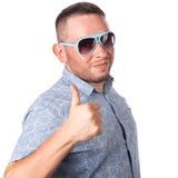 L'homme adulte attirant avec les lunettes de soleil de port de barbe dans la chemise d'été montre l'OK de geste Image libre de droits