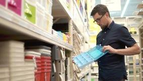 L'homme adulte avec des verres ouvre le nouveau récipient en plastique dans un supermarché banque de vidéos