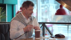 L'homme adulte dans une chemise blanche ajoute le sucre au café fait frais de matin clips vidéos