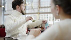 L'homme adulte donne le sac actuel à son amie dans un café clips vidéos