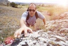 L'homme adulte escalade une montagne photo stock