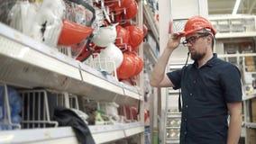 L'homme adulte essaye sur un chapeau protecteur pour le constructeur dans un magasin banque de vidéos