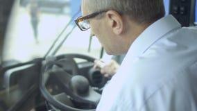 L'homme adulte inspecte la carlingue du ` s de tracteur banque de vidéos