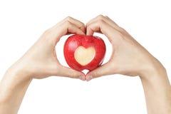 L'homme adulte remet tenir la pomme avec le coeur découpé Photographie stock libre de droits