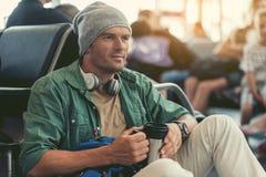 L'homme adulte songeur se repose dans le salon d'aéroport Photo stock