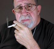 L'homme adulte sur l'oxygène fume dangereusement une cigarette Photo libre de droits
