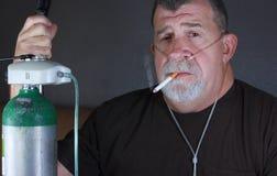 L'homme adulte sur l'oxygène fume une cigarette Image libre de droits