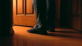 L'homme adulte tient la porte proche à une salle de bains la nuit Image libre de droits