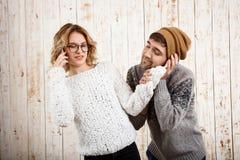 L'homme affaiblissent son amie parlant du téléphone au-dessus du fond en bois Photographie stock libre de droits