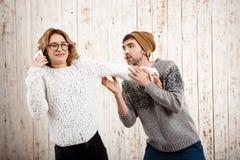 L'homme affaiblissent son amie parlant du téléphone au-dessus du fond en bois Photos libres de droits