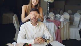 L'homme affectueux attend son amie dans le restaurant, elle vient fermant ses yeux avec ses mains, étreignant et banque de vidéos