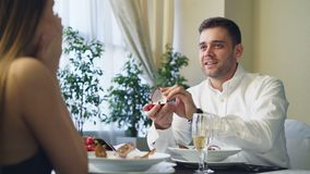 L'homme affectueux heureux dans la chemise blanche propose à la belle amie étonnée, donnant alors sa bague de fiançailles pendant banque de vidéos