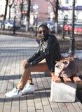 L'homme africain de concept de mode de rue avec le sac s'assied sur un banc en parc de ville Photo libre de droits