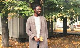 L'homme africain de sourire de mode dans le cardigan tricoté tient les feuilles jaunes d'érable en automne photos libres de droits