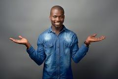 L'homme africain tenant le sien distribuent pour montrer des choix images stock