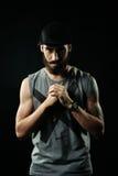 L'homme agressif avec des tatouages fléchissant ses poings Photographie stock libre de droits