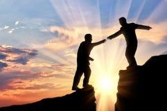 L'homme aide l'ami en montagnes de donner le coucher du soleil de coup de main Photographie stock