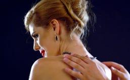 L'homme aide la femme à porter des bijoux Image libre de droits