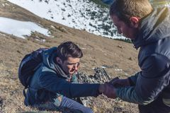 L'homme aide son ami à s'élever jusqu'au dessus Le randonneur donne une main pour tirer vers le haut sur la montagne images stock