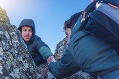 L'homme aide son ami à s'élever jusqu'au dessus Le randonneur donne une main pour tirer vers le haut sur la montagne photographie stock libre de droits