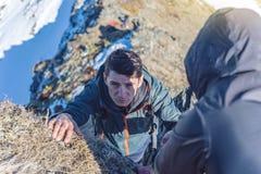 L'homme aide son ami à s'élever jusqu'au dessus Le randonneur donne une main pour tirer vers le haut sur la montagne image stock