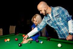 L'homme aide une fille à jouer la piscine sur la table de billard Photographie stock