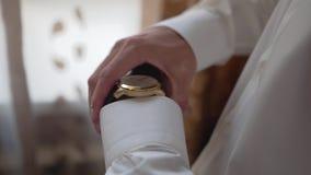 L'homme ajuste l'horloge sur sa main gauche Type chic banque de vidéos