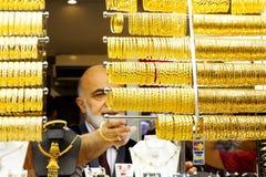 L'homme aligne des bracelets d'or Photos libres de droits