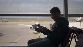 L'homme américain s'assied dans un aéroport dans un fauteuil et regarde un billet, dans le but de vérifier la porte, banque de vidéos