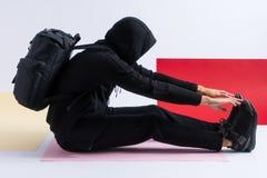 L'homme anonyme dans un hoodie noir avec le capot dessus et le sac à dos s'étire images stock