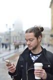 L'homme apprécie le téléphone et tenir une tasse de café Image libre de droits