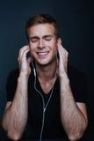 L'homme apprécie sa musique préférée avec la chemise noire de v-cou dessus photo libre de droits