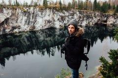 L'homme apprécient la belle vue de lac du hilltopl et le temps beau en Carélie Autour des roches Photos libres de droits