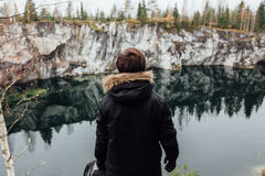 L'homme apprécient la belle vue de lac du hilltopl et le temps beau en Carélie Autour des roches Images stock