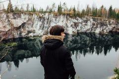 L'homme apprécient la belle vue de lac du hilltopl et le temps beau en Carélie Autour des roches Image stock