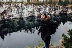 L'homme apprécient la belle vue de lac du hilltopl et le temps beau en Carélie Autour des roches Photos stock