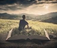 L'homme apprécient la vallée aux pages du livre, cru photos stock