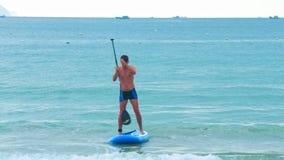 L'homme approche la position de plage d'océan sur le panneau de palette clips vidéos