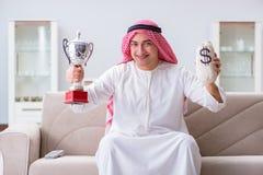 L'homme arabe avec le prix et argent sur le sofa Photo libre de droits