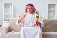 L'homme arabe avec le prix et argent sur le sofa Photo stock