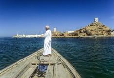 L'homme arabe de ferry transporte le passager dans un vieux bateau traditionnel Photos stock